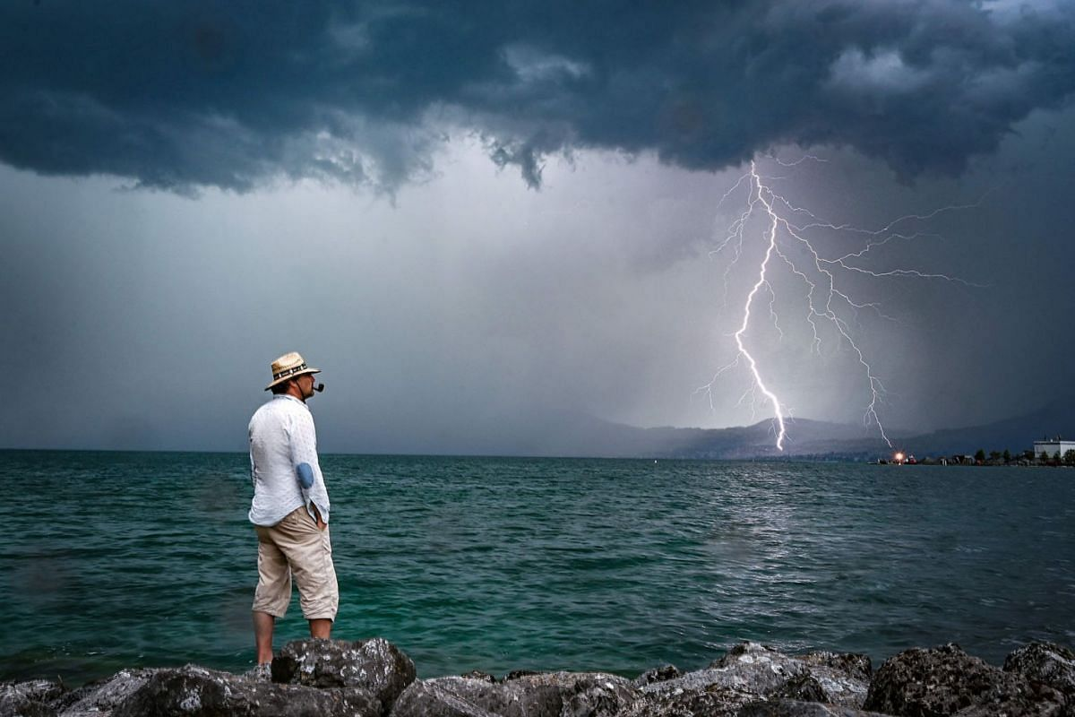 A man stands on rocks as lightning strikes over Lake Geneva on August 6, 2019 near Le Bouveret, western Switzerland. PHOTO: AFP