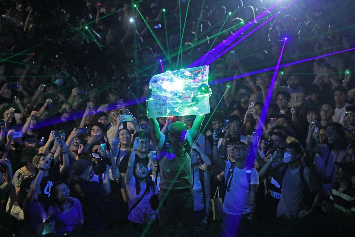 Protesters focus the laser pointers to a newspaper as they try to burn it, during a rally to demonstrate against the arrests of people caught in possession of laser pointers that police classified as offensive weapons because of their ability to harm