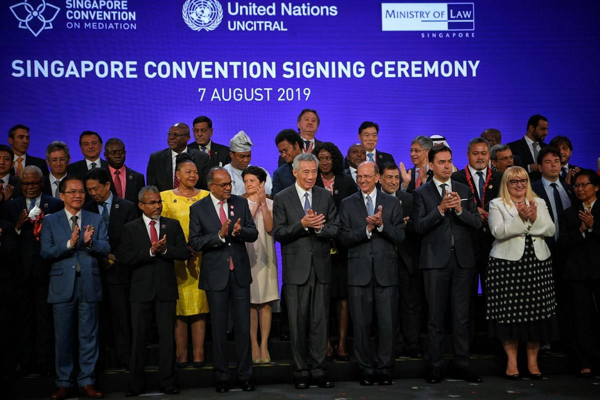 Prime Minister Lee Hsien Loong, flanked by Law and Home Affairs Minister K. Shanmugam and UN Assistant SecretaryGeneral for Legal Affairs Stephen Mathias, with signatories and heads of delegations after the signing of the Singapore Convention on Medi
