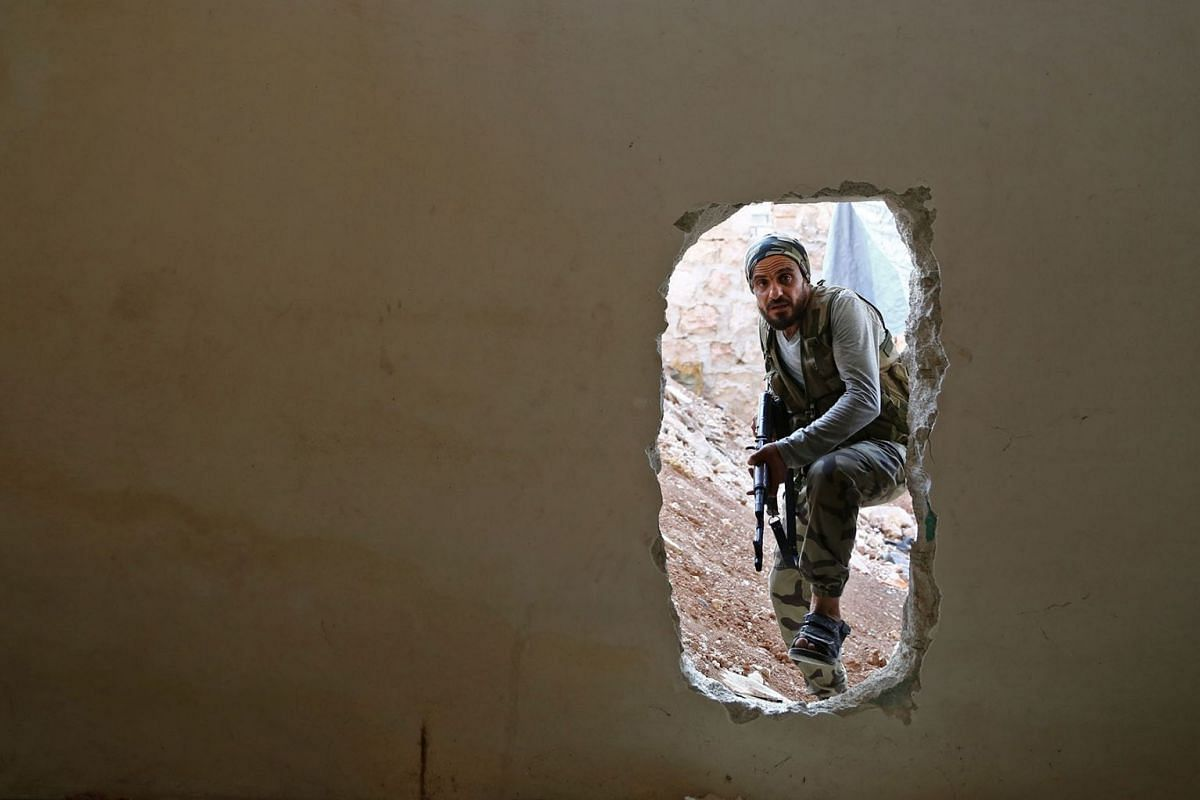 A Turkish-backed Syrian fighter crosses into a building through a hole in the wall in Tadef, near the city of al-Bab, in the eastern countryside of Aleppo province on August 6, 2019. PHOTO: AFP