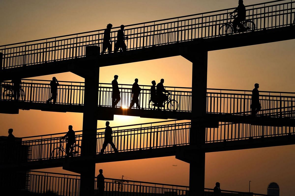 Asian labourers cross a pedestrian bridge in Dubai on August 7, 2019, as they head to work at a vegetable market. PHOTO: AFP