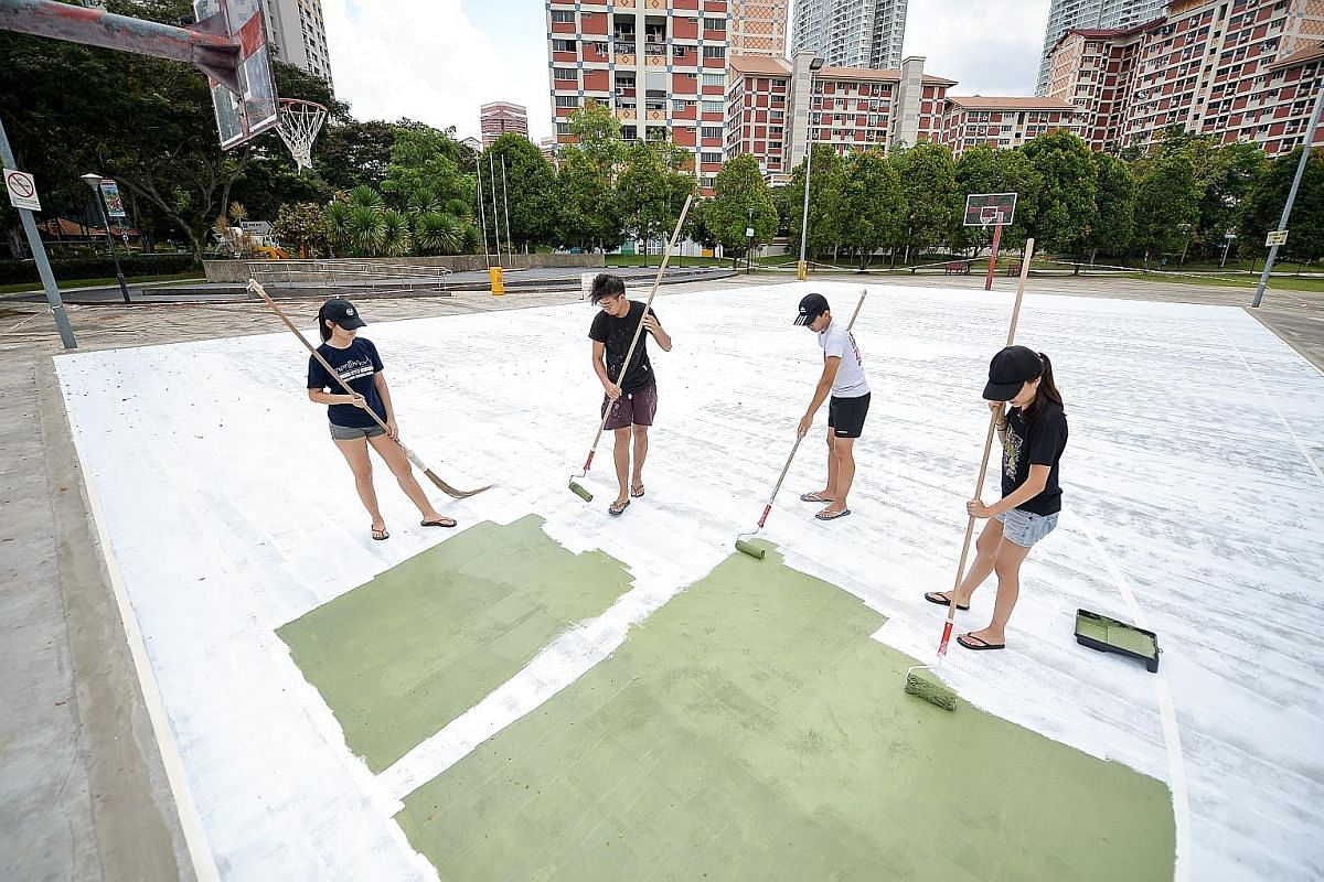 Mr Toby Tan (second from left) painting the Bishan basketball court as a team with his friends. This was similar to how he painted his first basketball court in Punggol - as a team and working up to nine hours a day.