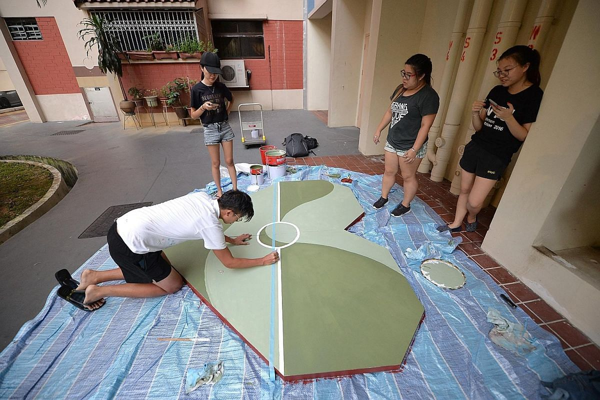 Mr Toby Tan painting a heart-shaped replica of the basketball court to promote his project, after being approached by Bishan North Community Centre to do so.