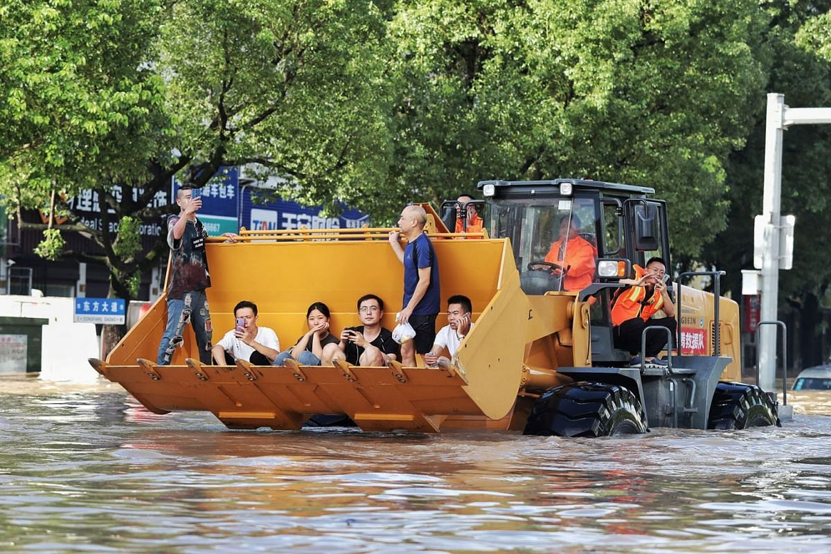Rescue workers evacuate stranded residents with a bulldozer on a flooded street after typhoon Lekima hit Taizhou, Zhejiang province, China, on Aug 11, 2019.