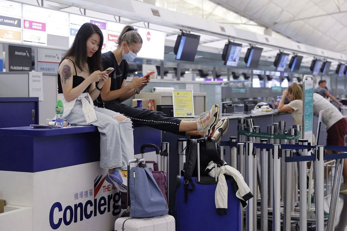 Stranded travellers from China (left) and Russia sit on the check-in counters at the Hong Kong International Airport, on Aug 12, 2019.