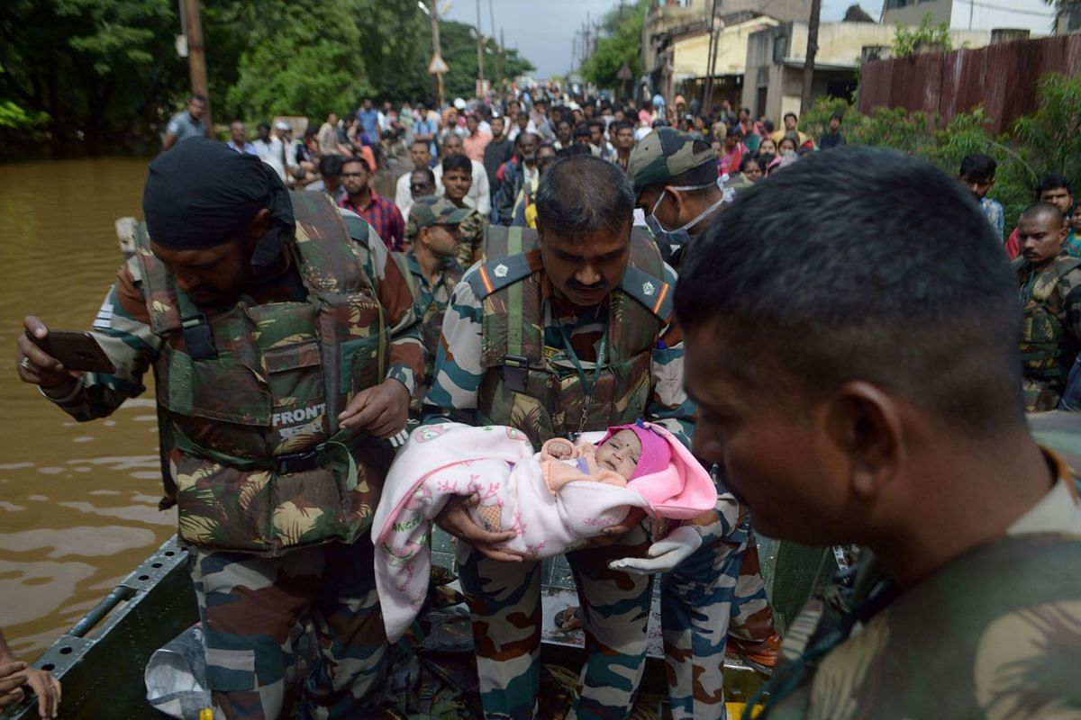 A soldier carries an infant as they evacuate flood-affected people to a safer place in Sangli district in the western state of Maharashtra, India, on Aug 11, 2019.
