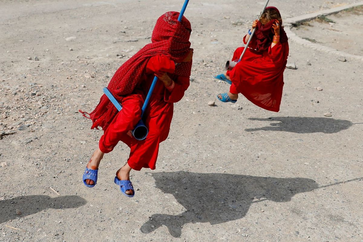 Afghan girls cover their faces as they ride on swings on the first day of the Muslim holiday of the Eid al-Adha, in Kabul, Afghanistan, on Aug 11, 2019.