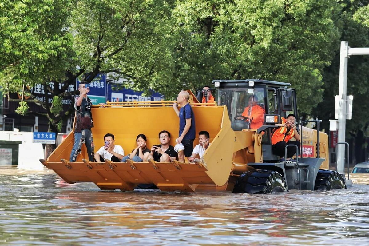 Rescue workers evacuating stranded residents with a bulldozer on a flooded street in Taizhou, Zhejiang province, on Aug 11, 2019.