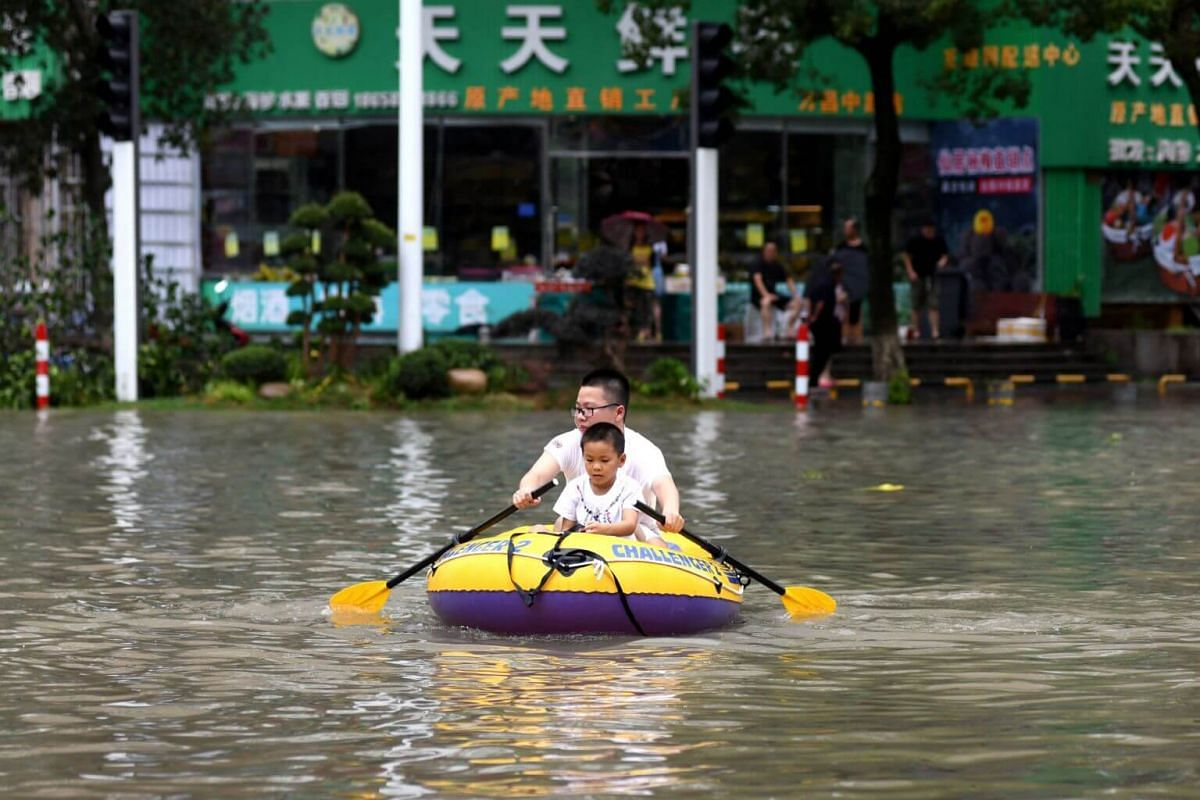 A man rowing an inflatable kayak with a boy in tow on a flooded street in Wenling, Zhejiang province, on Aug 10, 2019.