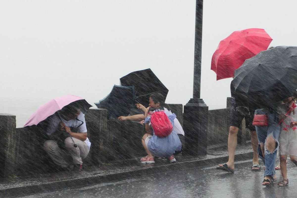 People using umbrellas to shelter themselves from heavy rain and large waves caused by Typhoon Lekima in Hangzhou, Zhejiang province, on Aug 9, 2019.