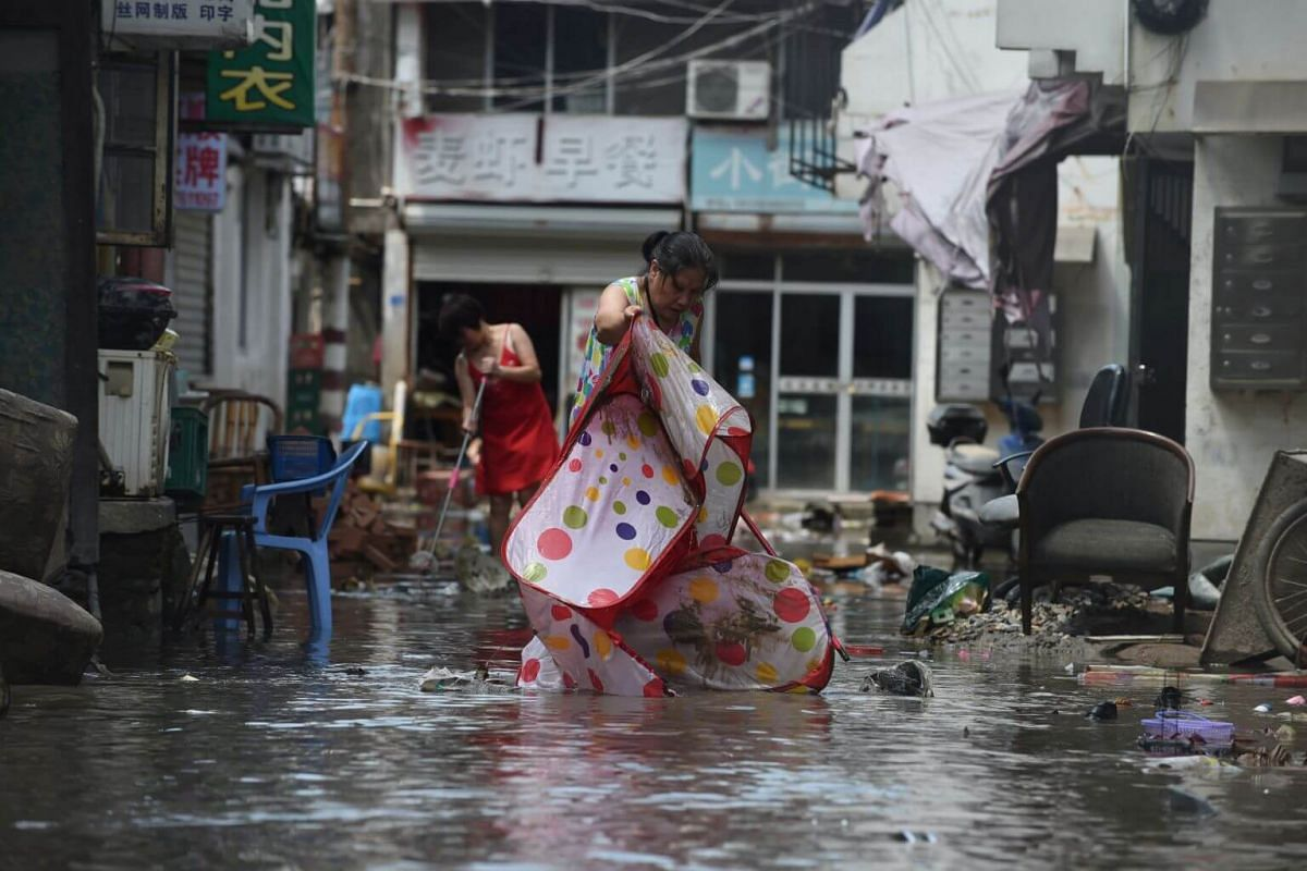 People clean a flooded street in Linhai city of Taizhou, Zhejiang province, on Aug 11, 2019.