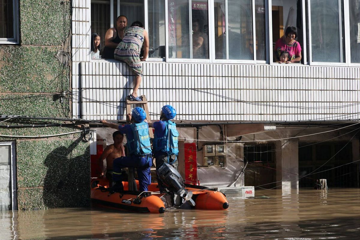 Rescue workers help residents stranded in a building partially submerged by floodwaters after Typhoon Lekima hit the city of Linhai in Taizhou, on Aug 11, 2019.