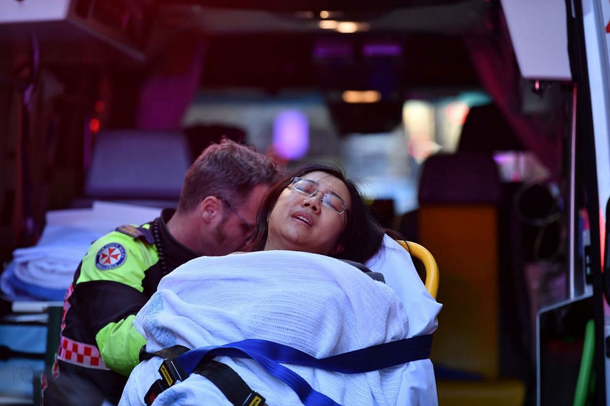 A woman is taken by ambulance, as police officers investigate a scene following reports of a stabbing in Sydney, Australia, August 13, 2019. PHOTO: AAP VIA REUTERS