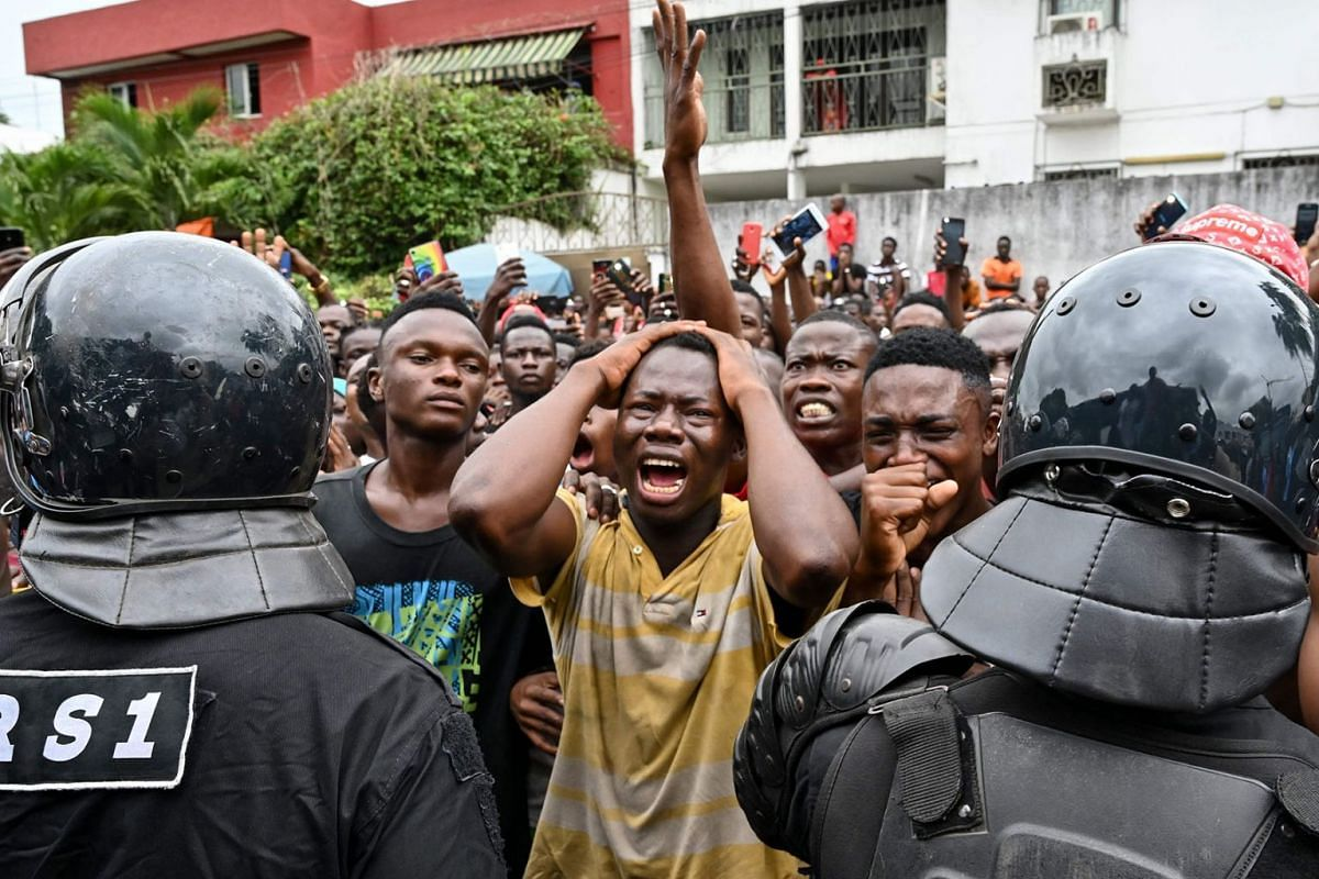"""Fans cry outside an hospital in Abidjan on August 12, 2019, after Ivorian singer DJ Arafat, star of the """"coupe-décale"""" and one of the most popular Ivorian artists, died at the age of 33 following a motorcycle accident overnight. PHOTO: AFP"""
