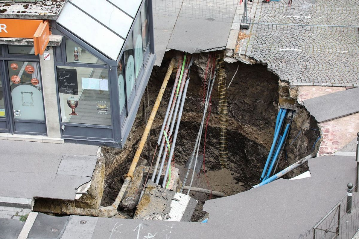 A sinkhole is seen along a street in the city of Amiens, northern France, on August 13, 2019. PHOTO: AFP