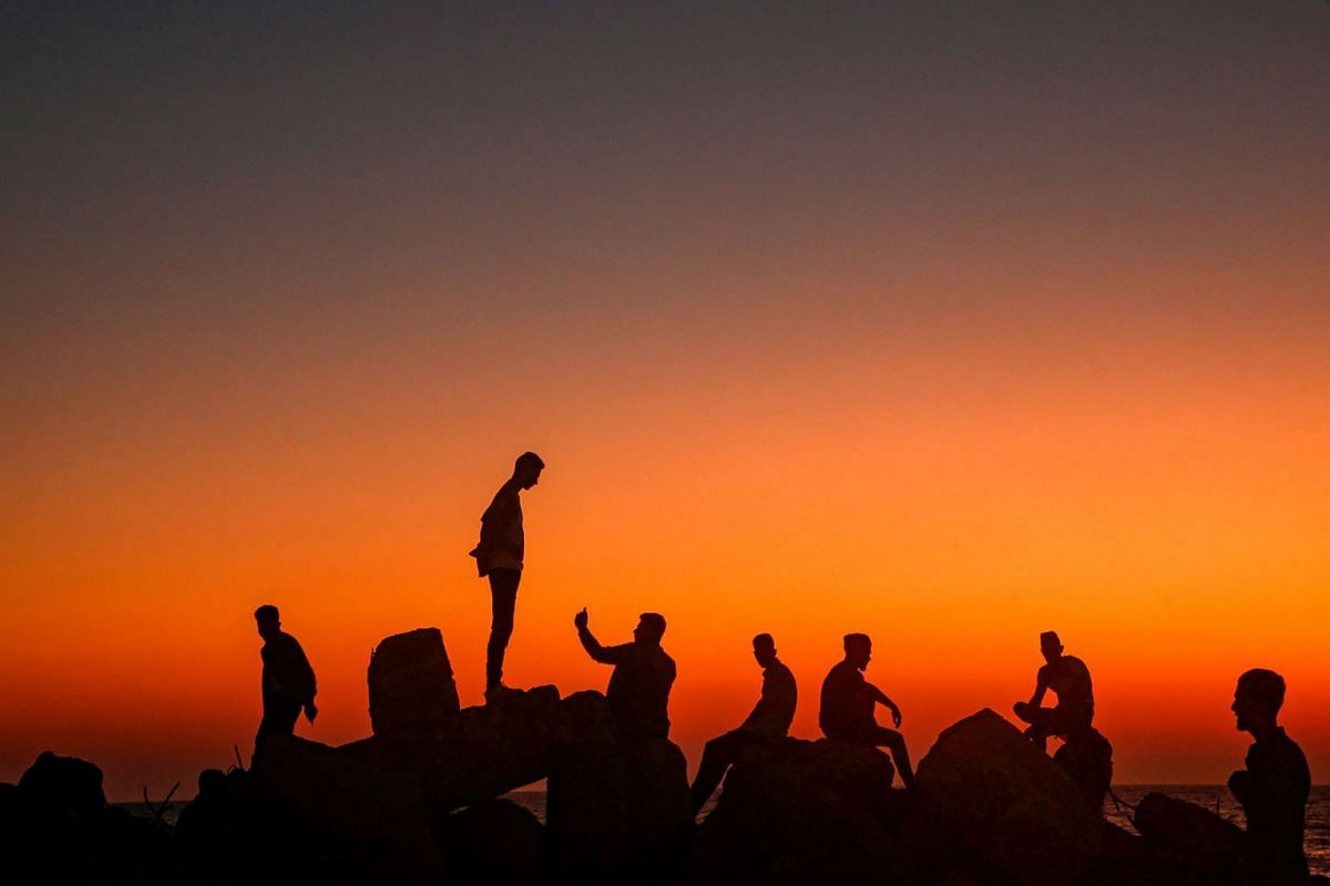 Palestinians sit and take pictures on the rocks by the Mediterranean in Gaza City on August 13, 2019, as people celebrate during the third day of the Muslim religious holiday of Eid al-Adha. PHOTO: AFP