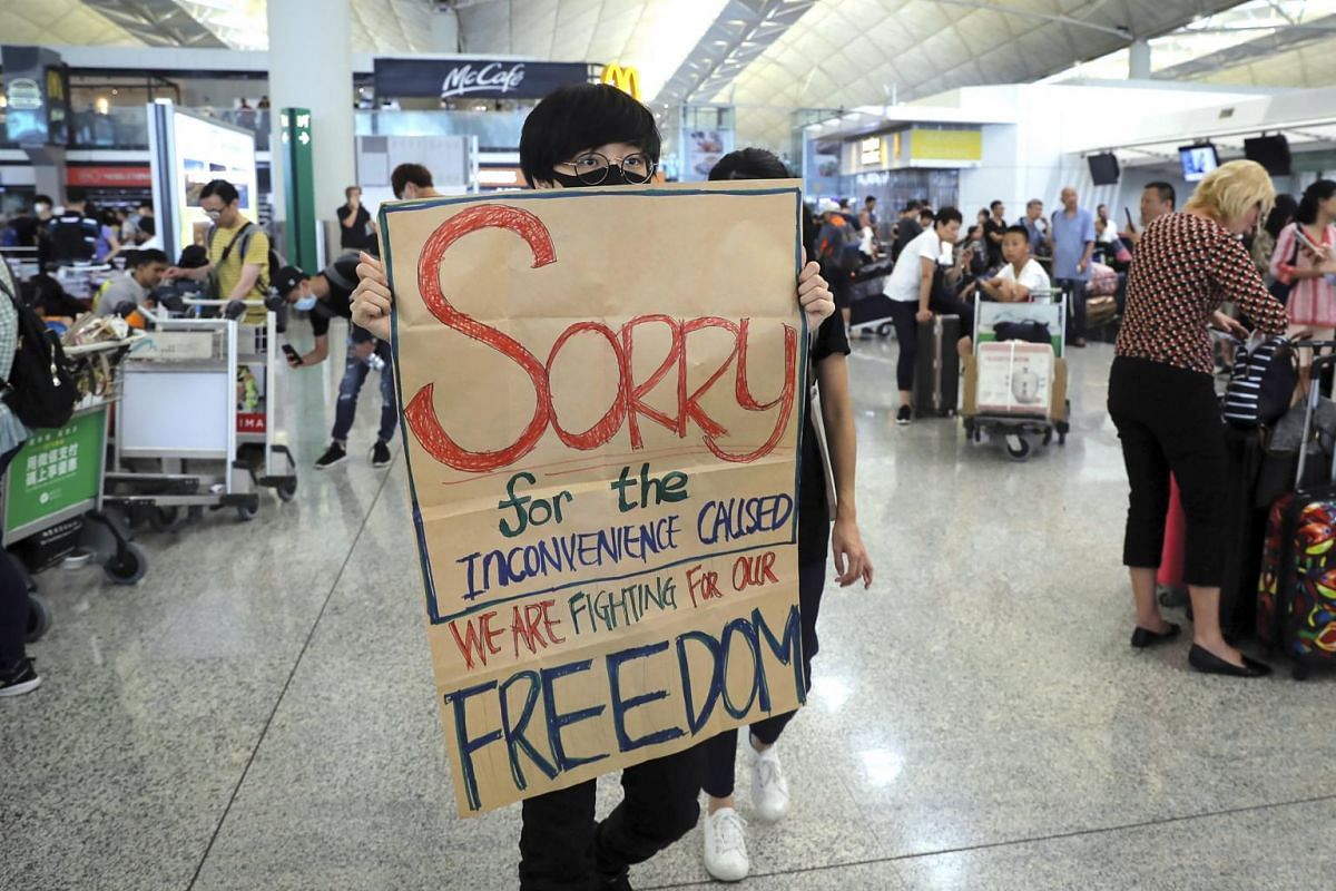 A protester shows a placard to stranded travellers during a demonstration at the airport in Hong Kong, on Aug 13, 2019.