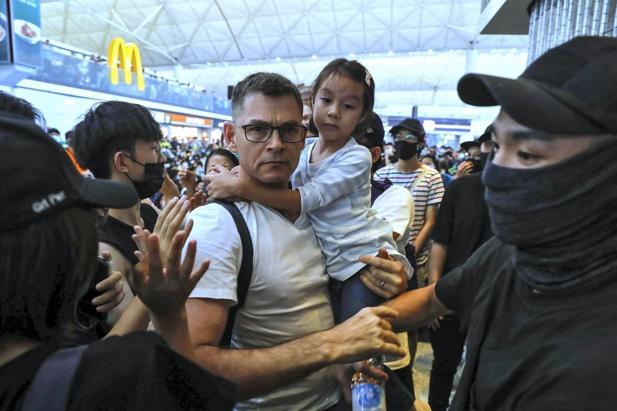 A traveller with a child tries to break through the crowd of protesters at the departure gate of the airport in Hong Kong, on Aug 13, 2019.