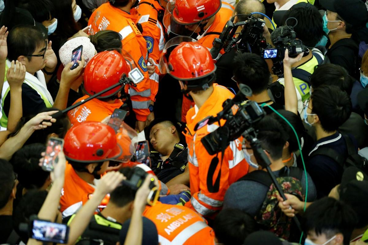 Medics attempt to remove an injured man who anti-government protesters say was an undercover policeman at the airport in Hong Kong, on Aug 13, 2019.