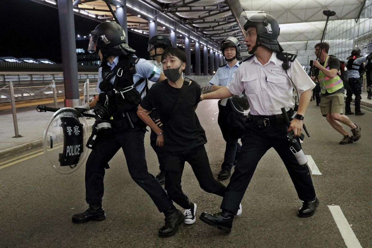 Policemen arrest a protester during a clash at the airport in Hong Kong, on Aug 13, 2019.