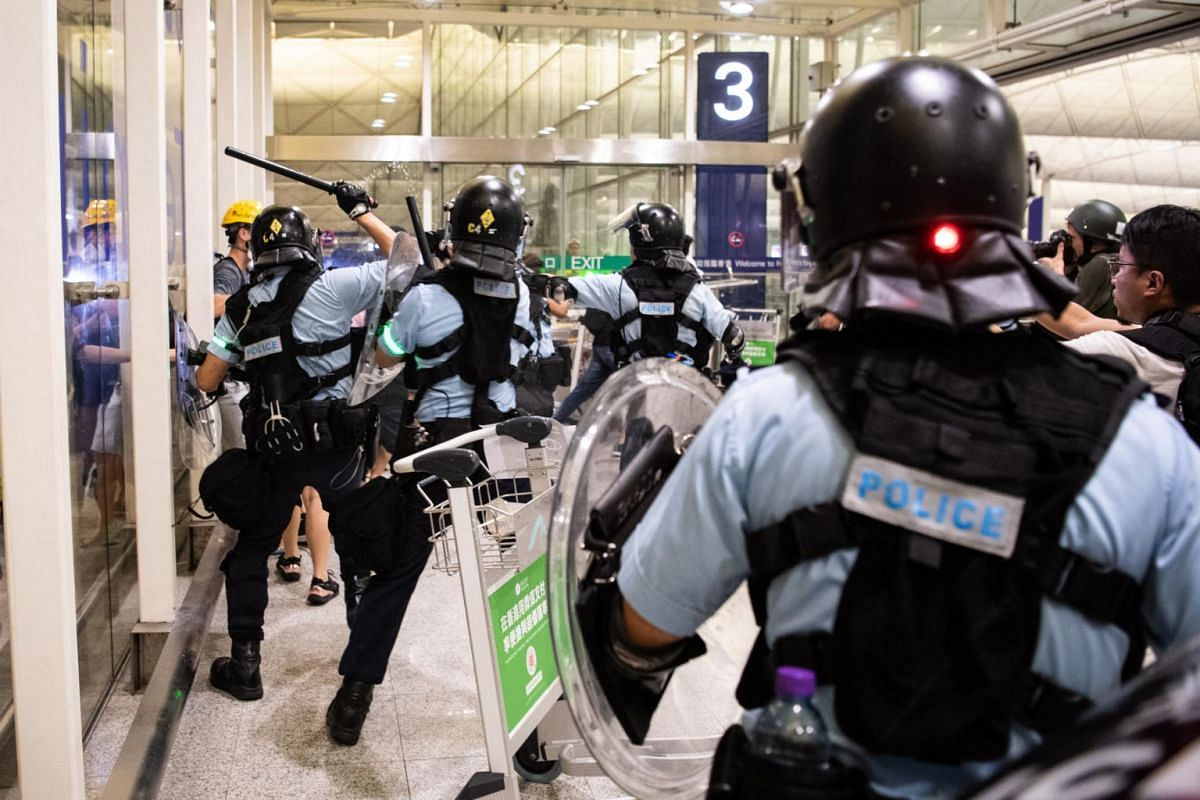 Riot police clash with anti-government protesters in Hong Kong International Airport, on Aug 13, 2019.