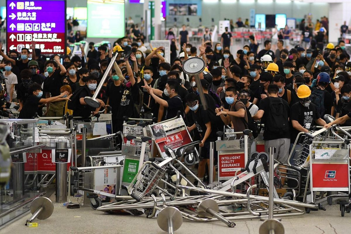 Pro-democracy protesters block the entrance to the airport terminals after a scuffle with police at Hong Kong's international airport, on Aug 13, 2019.
