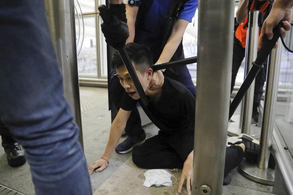 Policemen arrest a protester during a demonstration at the airport in Hong Kong, on Aug 13, 2019.