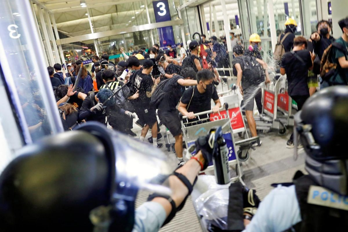 Riot police use pepper spray to disperse protesters during a mass demonstration at the Hong Kong international airport, on Aug 13, 2019.