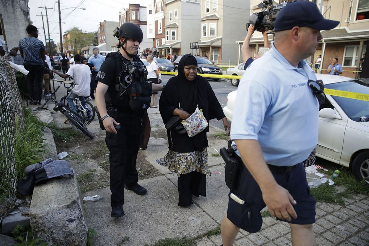 Police officers escort a bystander away from the scene of a shooting, Wednesday, Aug. 14, 2019, in the Nicetown neighborhood of Philadelphia. PHOTO: AP