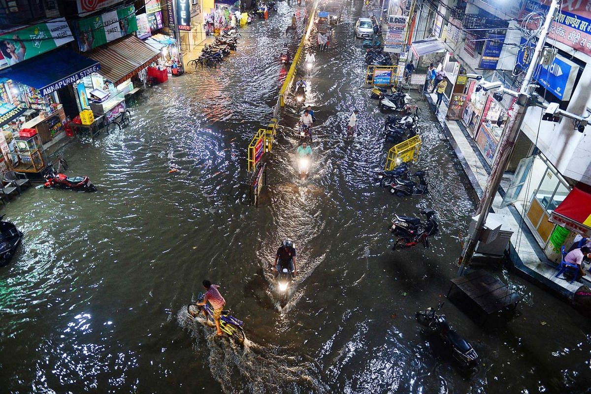 Commuters make their way through a flooded street after heavy rains in Allahabad on August 13, 2019. PHOTO: AFP