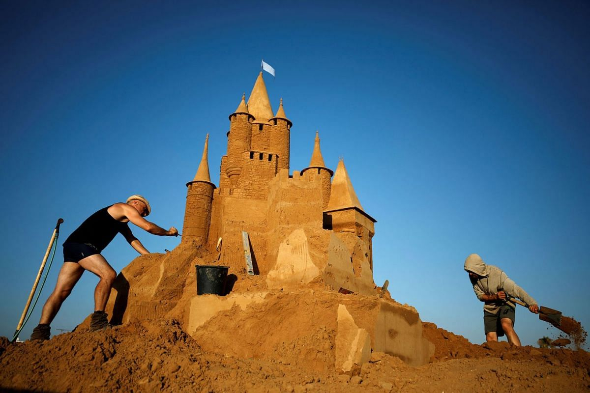 A photo issued on August 15, 2019 shows Enguerrand David of Belgium and Leonardo Ugolini of Italy working on their fairytale sand sculptures ahead of the opening of an International Sand Sculpture Festival in Ashkelon, Israel August 7, 2019. PHOTO: R