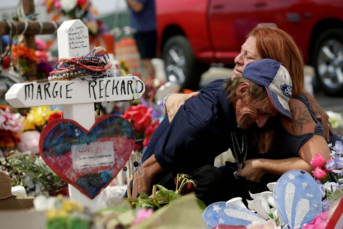 Antonio Basco, whose wife Margie Reckard was murdered during a shooting at a Walmart store, is comforted by a woman next to a white wooden cross bearing the name of his late wife, at a memorial for the victims of the shooting in El Paso, Texas, U.S.