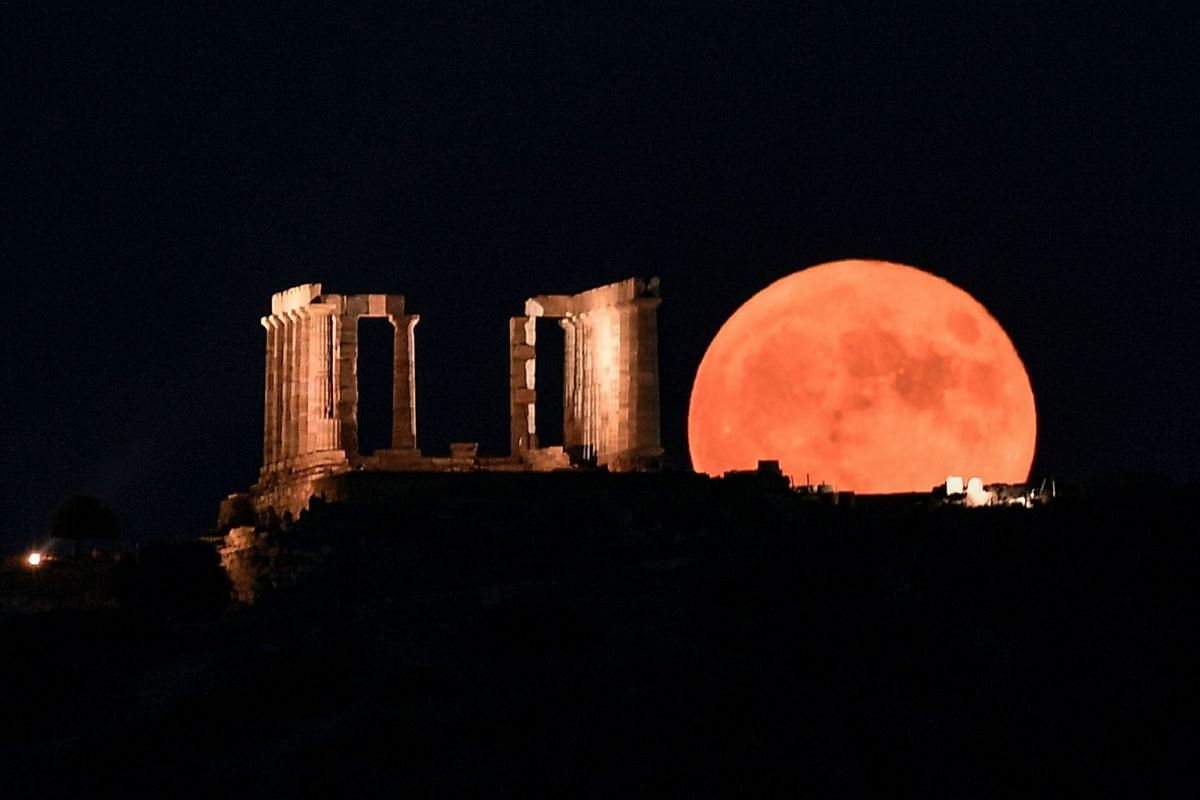 The full moon rises next to the Poseidon Temple at the Cape of Sounion, some 70 km south of Athens, on August 15, 2019. PHOTO: AFP