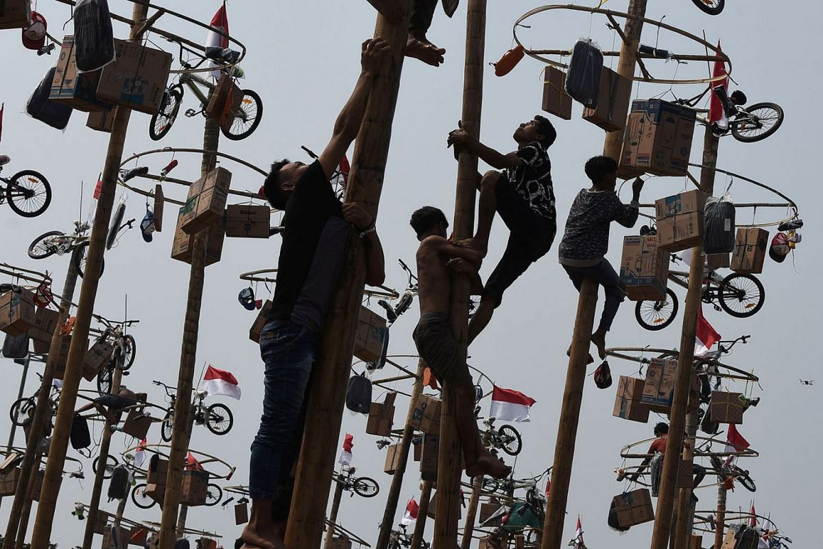 Participants climb greased poles to reach the prizes during a Panjat Pinang competition to celebrate Indonesia's 74th Independence Day at Ancol beach in Jakarta, Indonesia, on Aug 17, 2019.