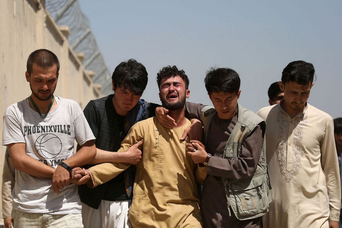An Afghan man mourns during the funeral of his brother after a wedding suicide bomb blast in Kabul, Afghanistan, on Aug 18, 2019.