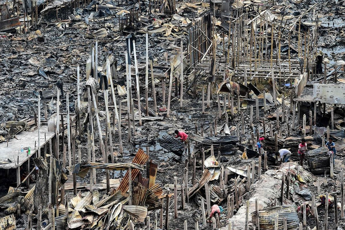 A resident gathers charred debris in a slum in Dhaka, Bangladesh, on Aug 18, 2019, after a fire broke out late the day before at Mirpur neighbourhood.
