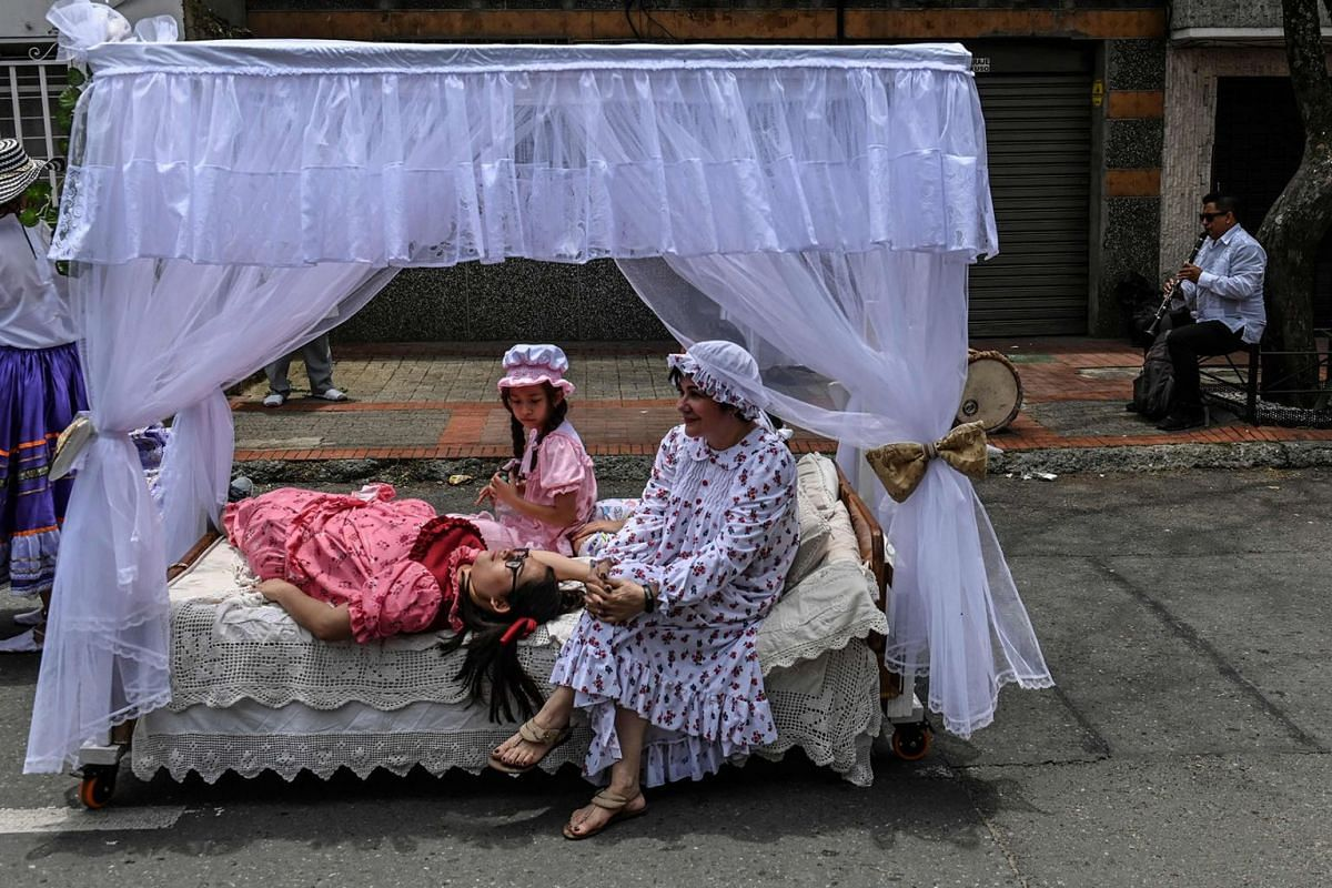 Women lay in bed nearby a man playing some music while celebrating the World Day of Laziness in Itagui, near Medellin, Colombia, on Aug 18, 2019.