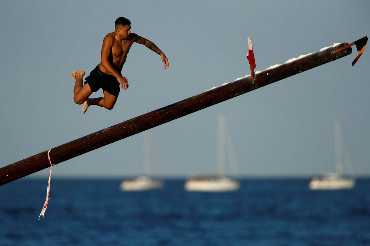 """A competitor falls off the """"gostra"""", a pole covered in lard, during the week-long celebrations of the religious feast of St Julian, patron of the town of St Julian's, Malta, on Aug 18, 2019."""