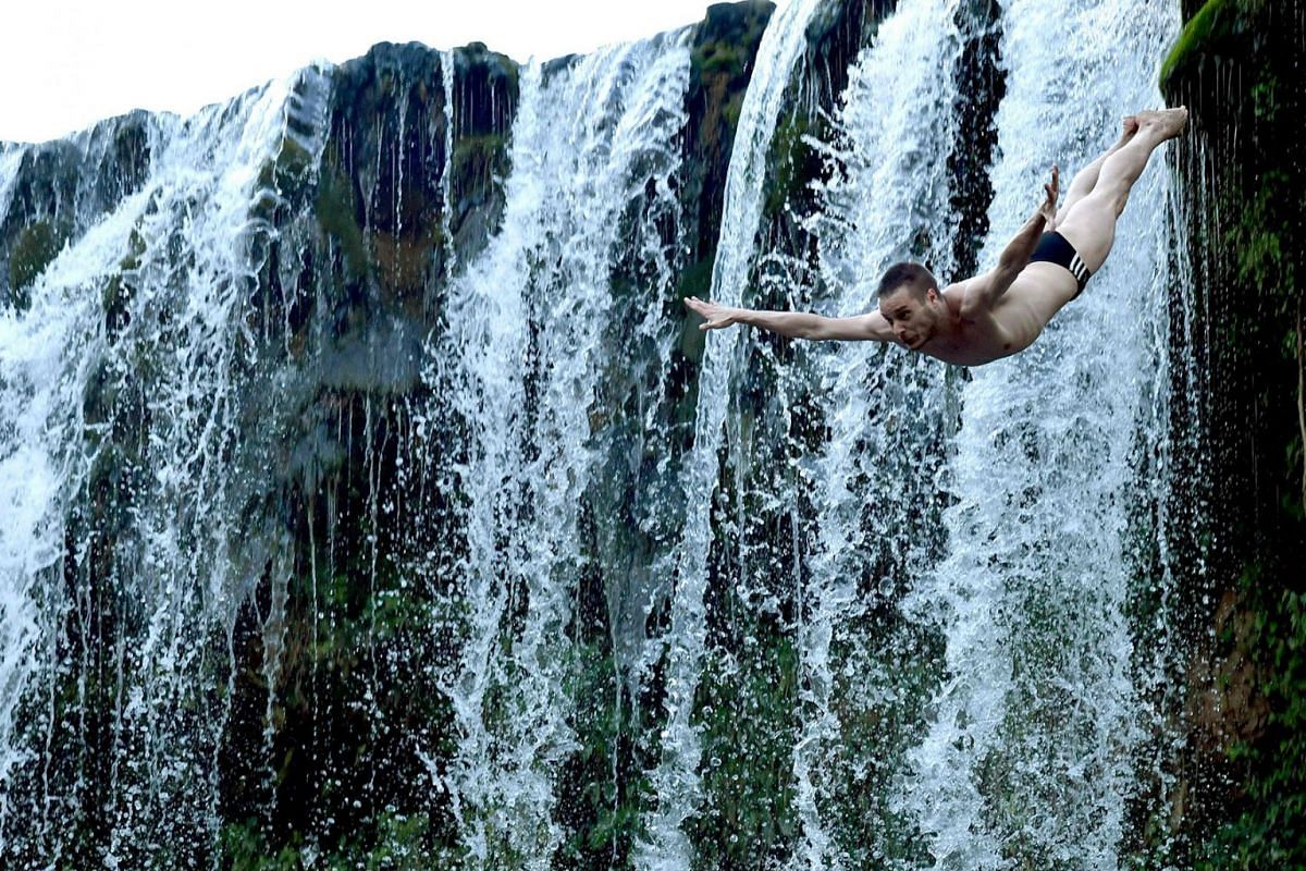 A high diver takes off from the 22m-high Pliva river waterfall in the Central-Bosnian town of Jajce during the fifth annual Waterfall Dive competition on Aug 17, 2019.