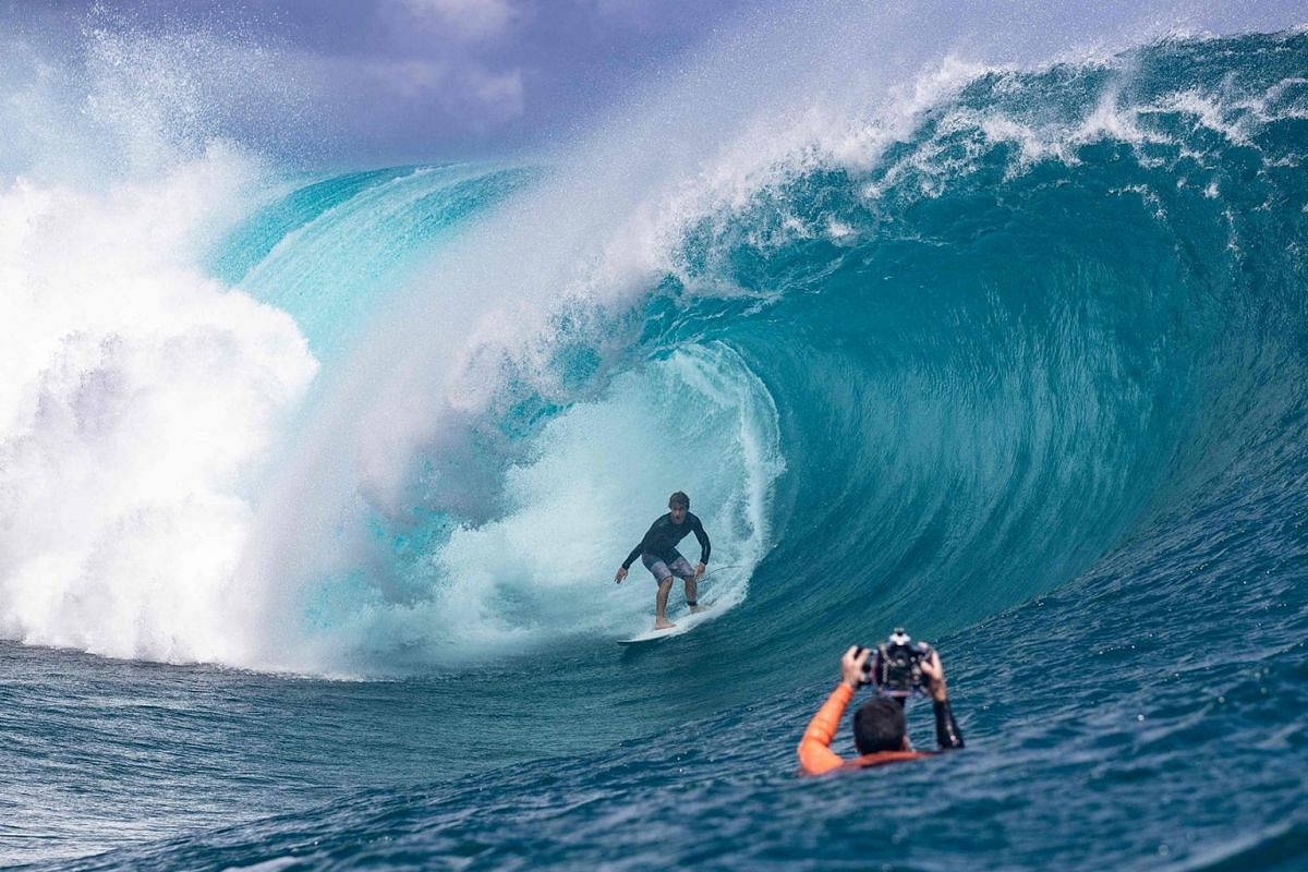 US surfer Benji Brand from Hawaii practises next to a photographer taking pictures ahead of the Tahiti pro surfing trial at the famous break Teahupoo in Tahiti, French Polynesia, on Aug 18, 2019.