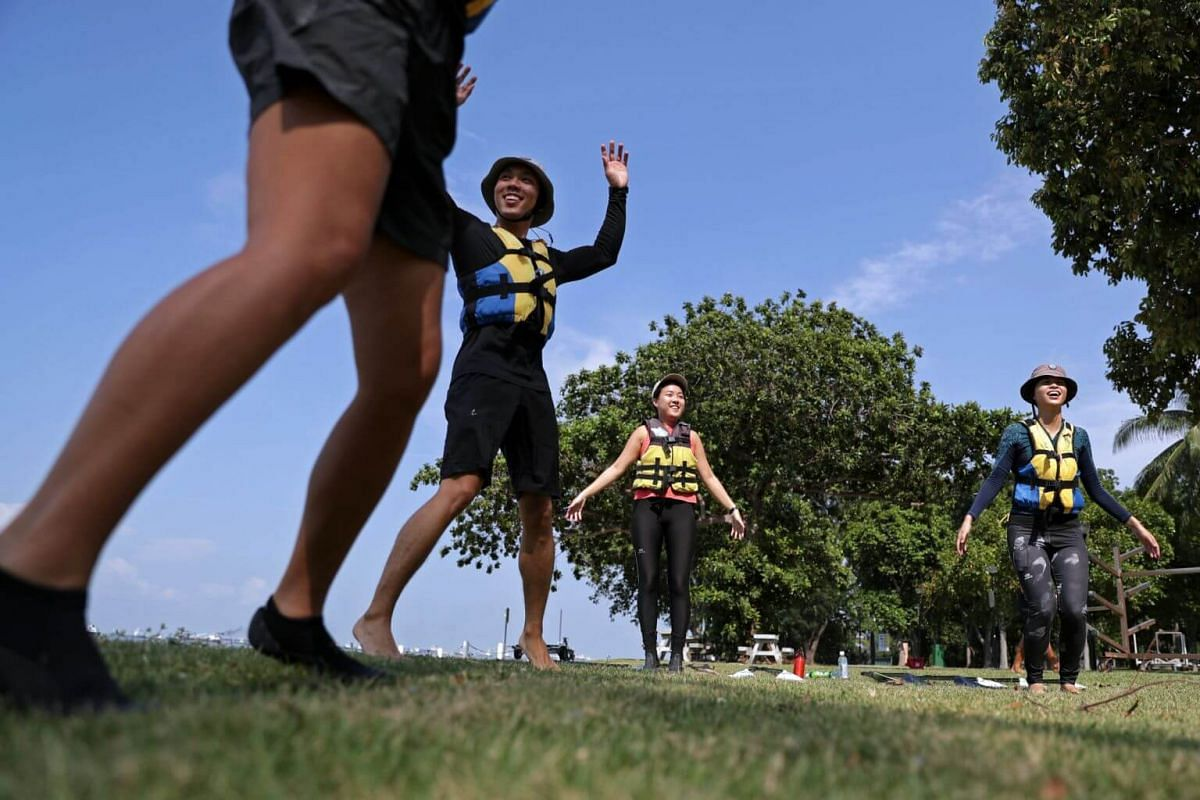 Stand up paddling interest group members (from right) Tracy Chien, Amanda Choo, Yeung Zhen Bang and Kelly Chong warm up before launching their paddle boards into the water at East Coast Park for a lagoon paddle and cleanup session on July 14.
