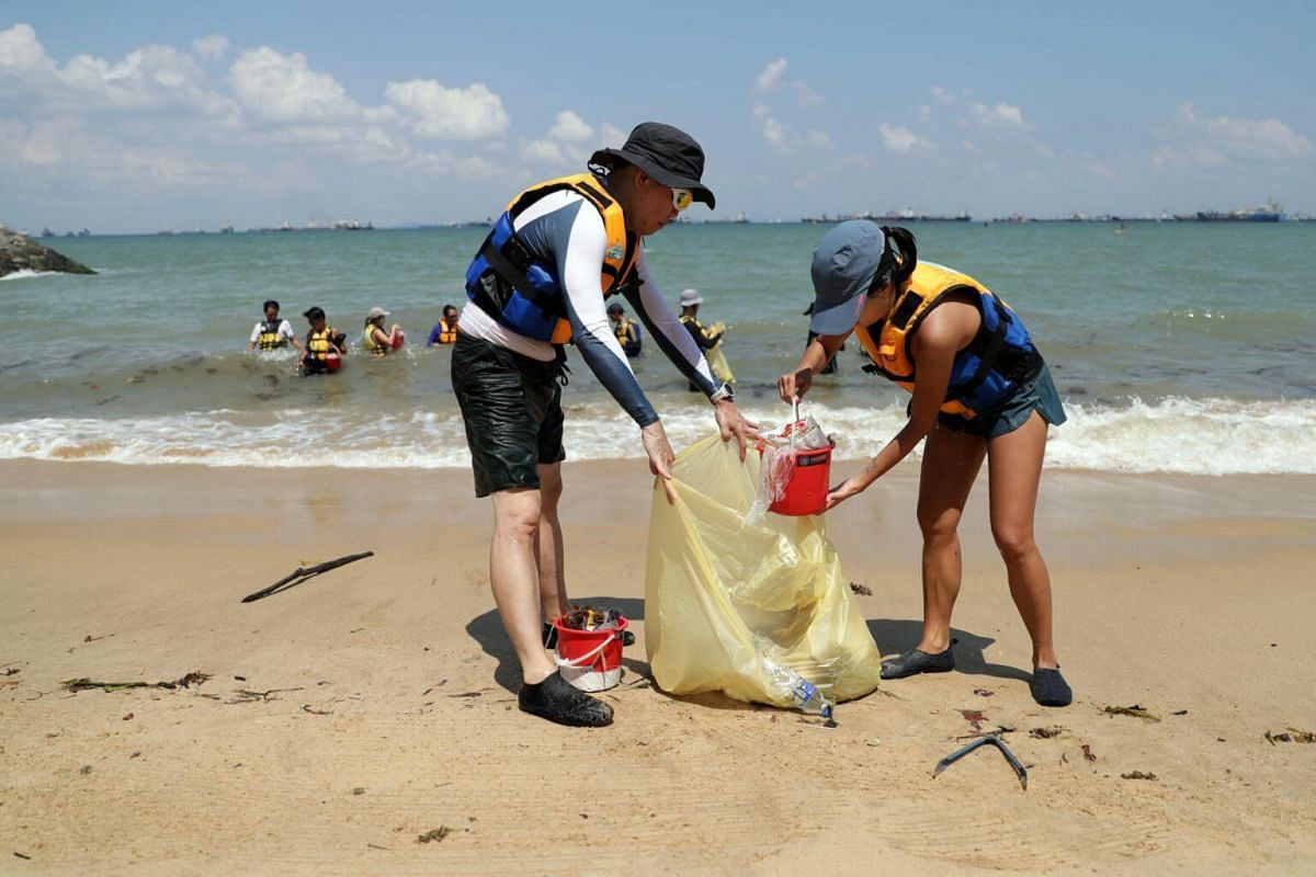 Mr Damien Goh (left) and Ms Jessica Wee (right) put the rubbish they picked up from the waters along the shore into a trash bag to be deposed off at the outlet.