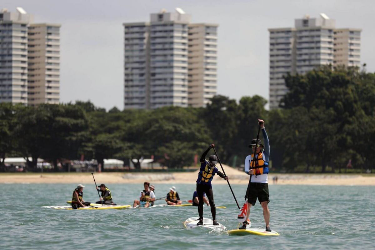 Mr Damien Goh (extreme right) and Mr Ng Boon Yeow (second from right) balance on their paddle boards as the rest of the stand up paddling interest group members take a break during a lagoon paddle and cleanup session at East Coast Park on July 14.