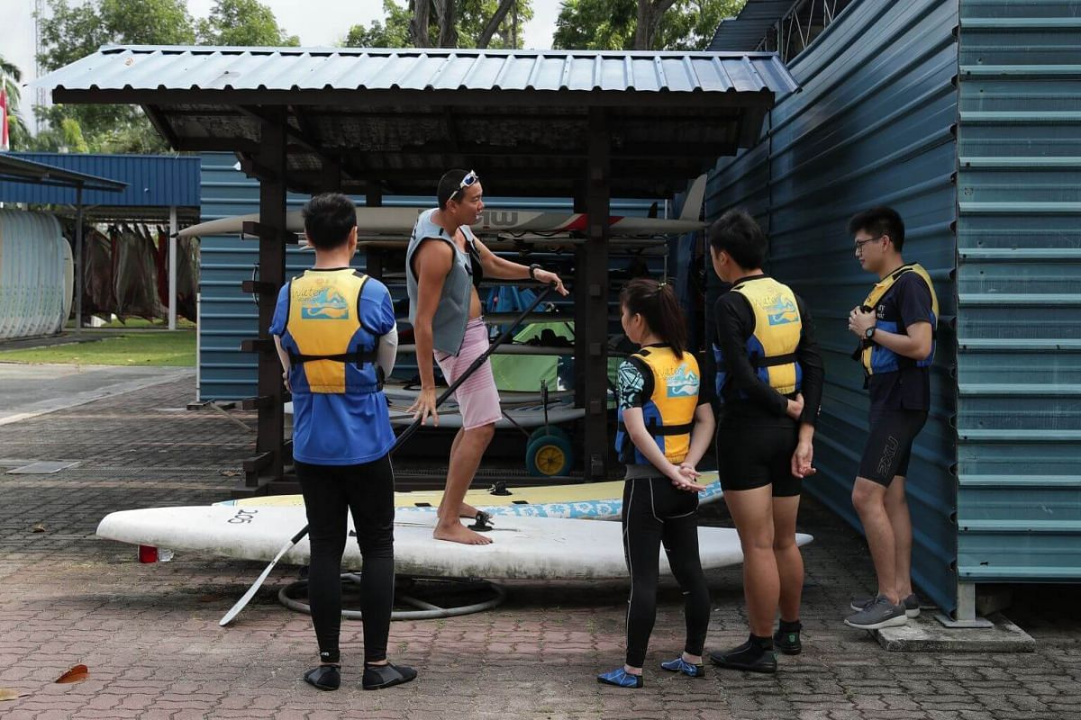 Trainer Justin Chua (second from left) conducts a stand up paddling starter course for beginners at PAssion WaVE at East Coast on June 30.