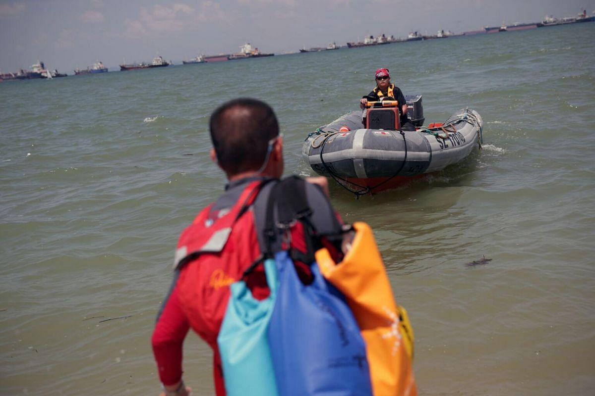 Safety boat officer Ms Ng Li Bing brings the powerboat close to shore to pick up the bags and personal belongings of the stand up paddling interest group members.