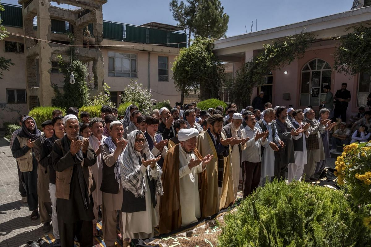 Prayers are held next to the bodies of two of the people killed Saturday during a suicide bombing at a wedding in Kabul, Afghanistan, on Aug 18, 2019.