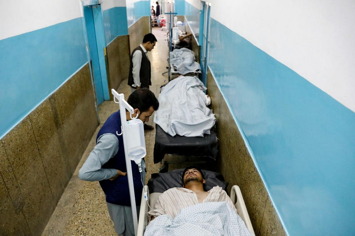 Injured men receive treatment in the hospital after sustaining wounds from a blast at a wedding hall in Kabul, Afghanistan, on Aug 18, 2019.