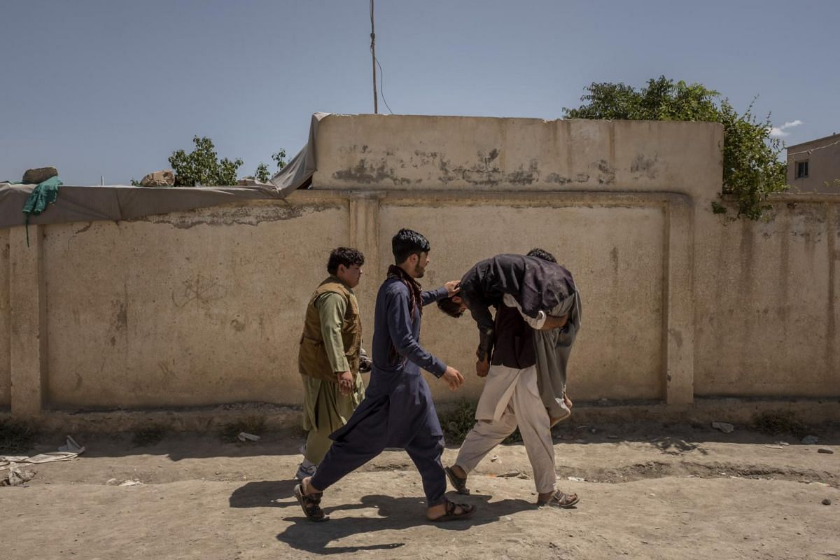 A young man who fainted is carried to the shade during a group funeral for people killed on Saturday during a suicide bombing at a wedding in Kabul, Afghanistan, on Aug 18, 2019.