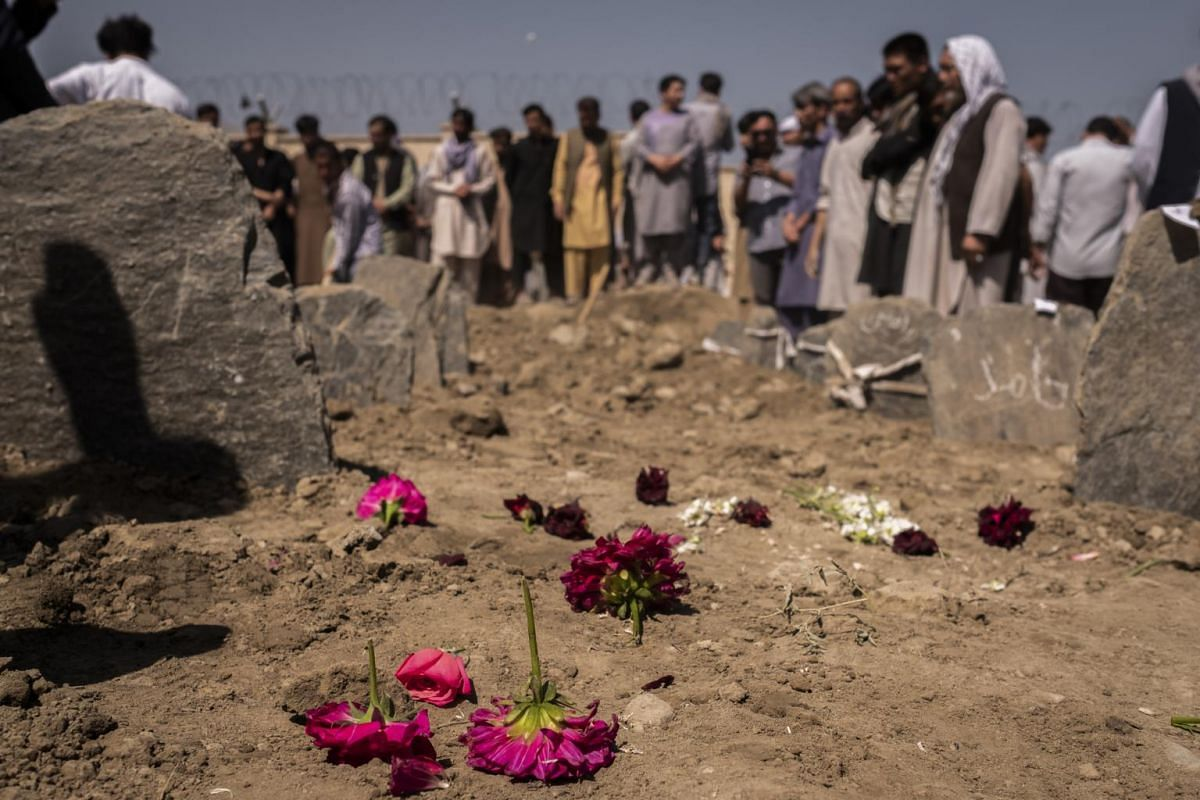 Flowers on the graves of people killed on Saturday in a suicide bombing at a wedding in Kabul, Afghanistan, on Aug 18, 2019.