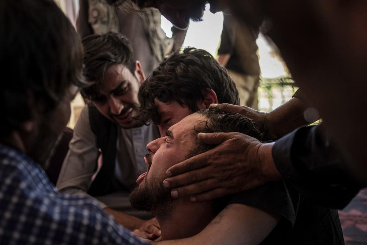 A cousin of the bride, who lost his brother in Saturday's suicide bombing at a wedding, collapses during a group funeral in Kabul, Afghanistan, on Aug 18, 2019.